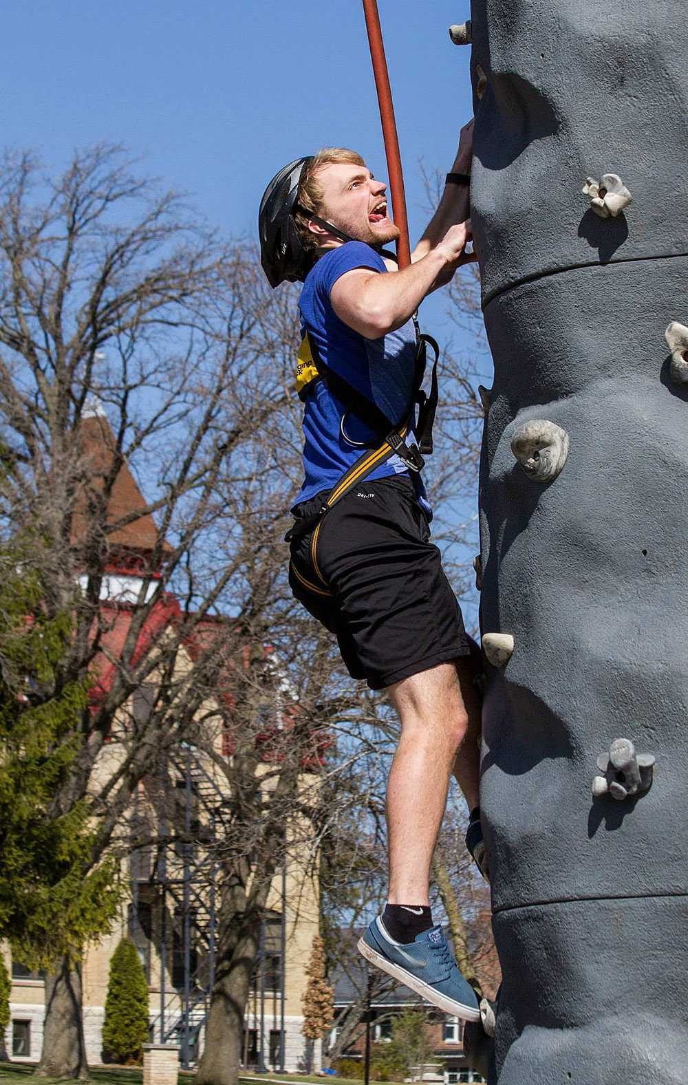 Student Josh Mann scales the rock climb.