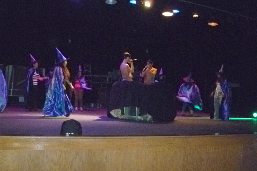 Witches practice their dance in front of the cauldron.