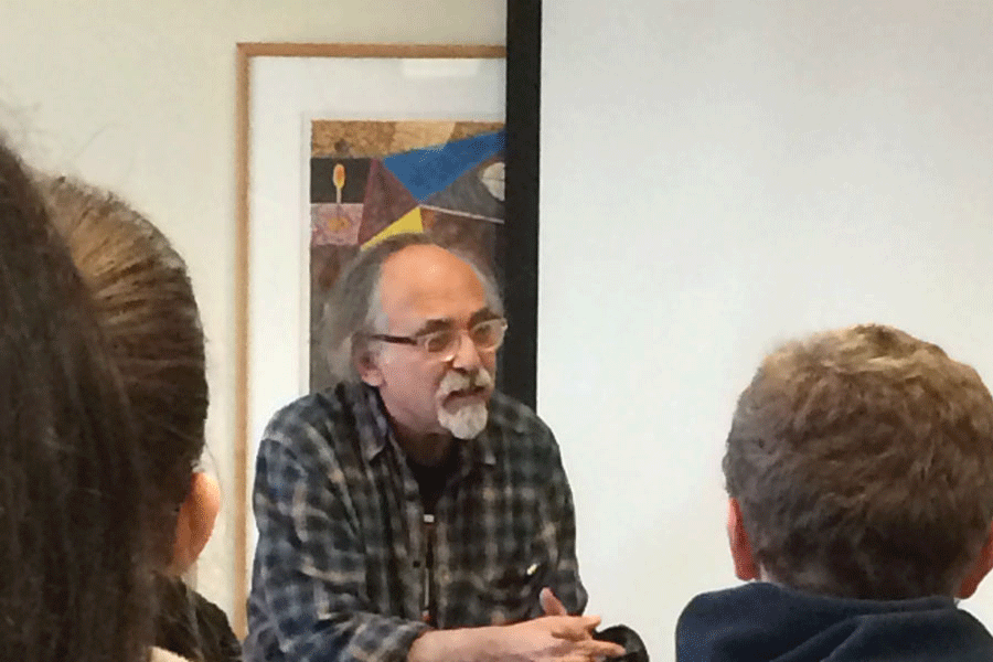 Art Spiegelman sits on the back of a chair to get a better view of the people in the back of the room during the question and answer session.