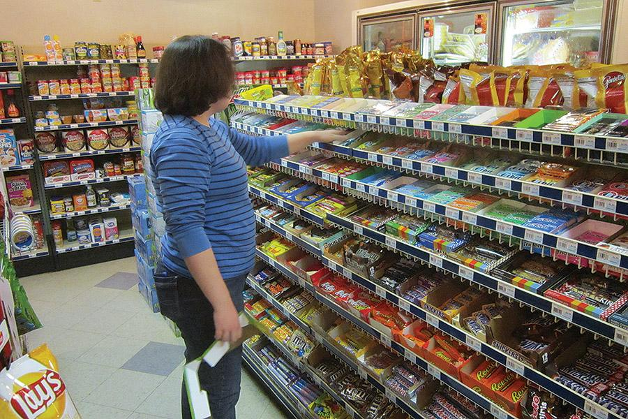 A student worker restocks and reprices the Muskie Mart's large variety of gum and candy bars.