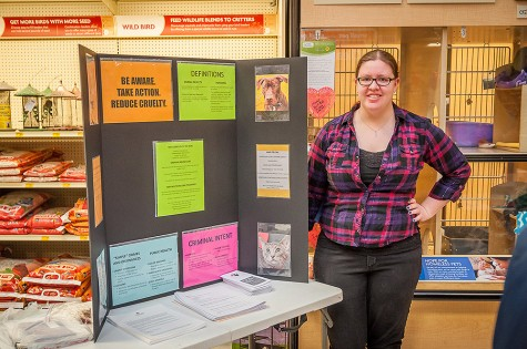 Lindsay Kleckner, senior criminal justice major, stands by her display at the Sheboygan PetSmart during an adoption event with the Sheboygan County Humane Society.