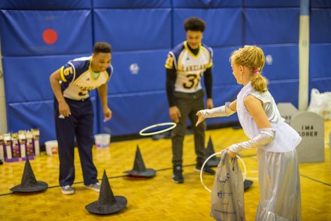 Sophomore Michael Whitley (left) and Freshman Eddie Strickland (right) cheer on a child at Lincoln-Erdman Elementary School's Halloween event.
