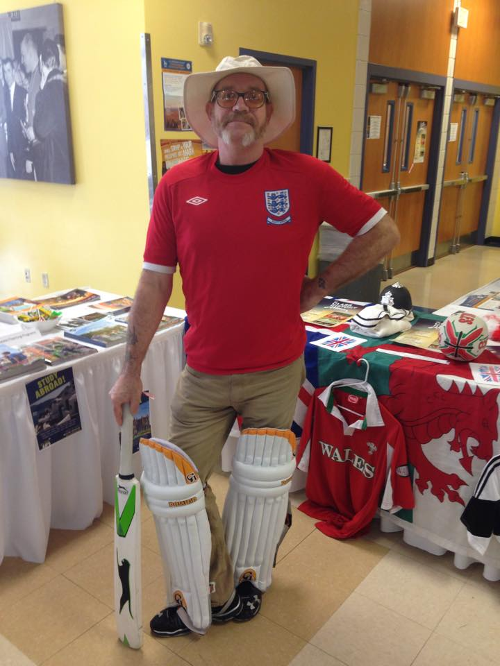 Rick Dodgson, Associate Professor of History, stands with cricket bat at the Study Abroad table in Bossard to help promote International Education Week.