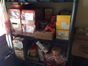 One of two small storage racks in the Muskie Mart storage room, holding ramen and chips.