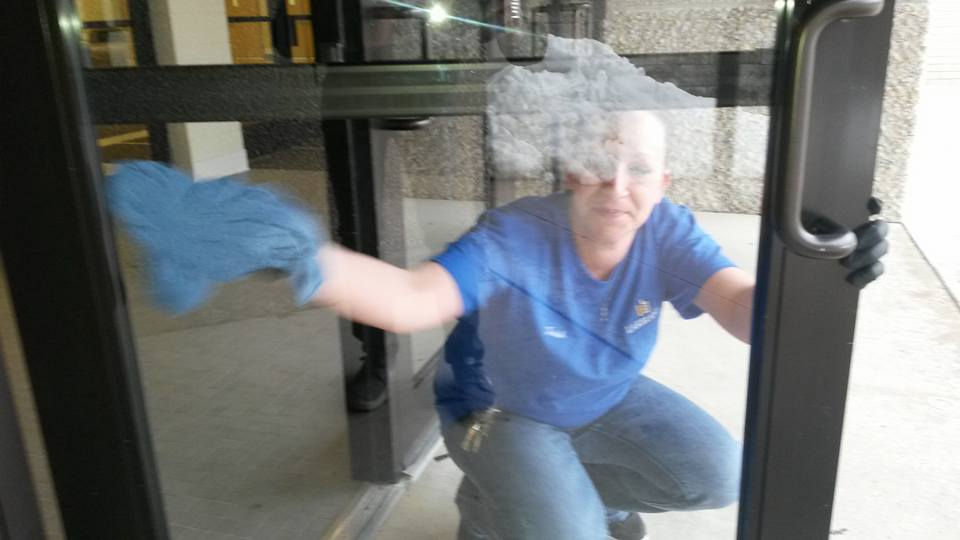 Custodian Patricia Heinrich washes hand prints off of the Wehr Center doors.