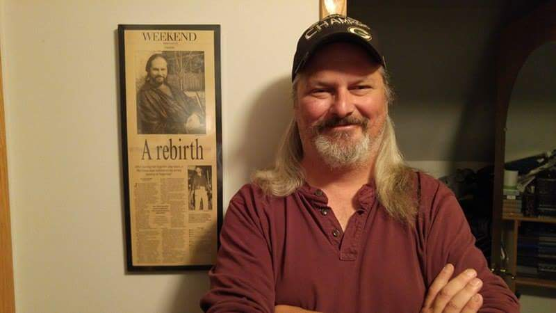 """Scott Kindschi, a volunteer advisor to the LU improv group, standing by an article celebrating his return to theater as the role of Jesus in """"Jesus Christ Superstar"""" after a nine-year absence."""