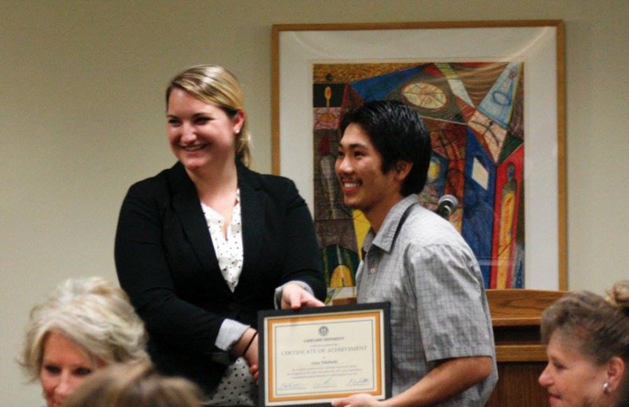Success coach Mara Poullette hands graduating senior exercise science major Casey Takahashi a plaque.